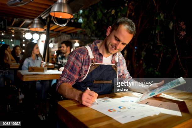 Gelukkig ondernemer bij een restaurant dat doet de boeken