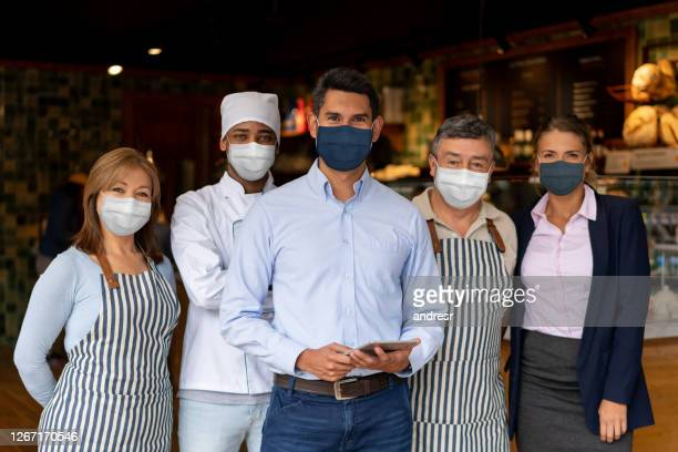 happy business owner at a restaurant with his staff wearing a facemask - biosecurity stock pictures, royalty-free photos & images