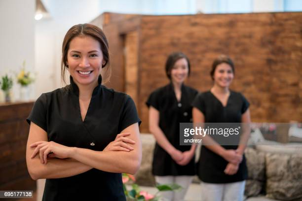 happy business owner at a spa with a group of workers - massage therapist stock pictures, royalty-free photos & images