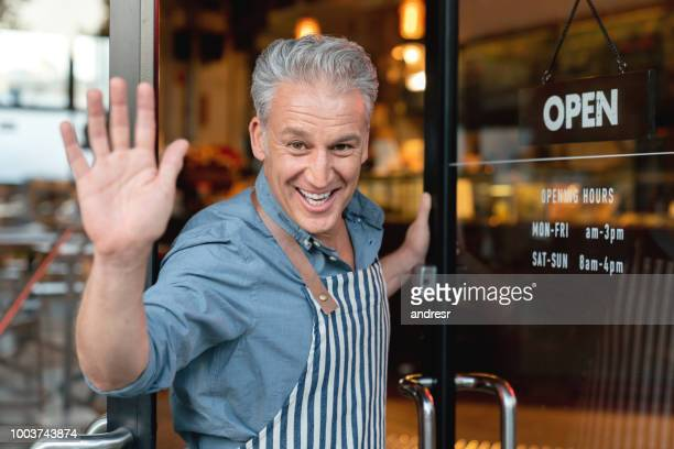 happy business owner at the door of a cafe waving to the camera - waving stock pictures, royalty-free photos & images