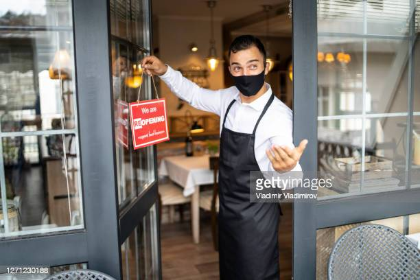 happy business owner hanging a we're reopening sign - opening event stock pictures, royalty-free photos & images