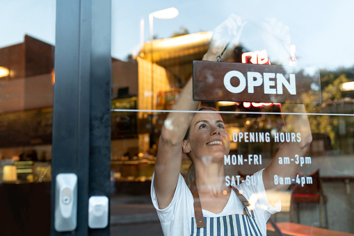 Happy business owner hanging an open sign at a cafe 1003743872