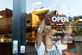 Happy business owner hanging an open sign at a cafe