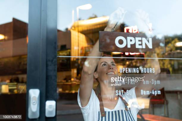 happy business owner hanging an open sign at a cafe - business imagens e fotografias de stock
