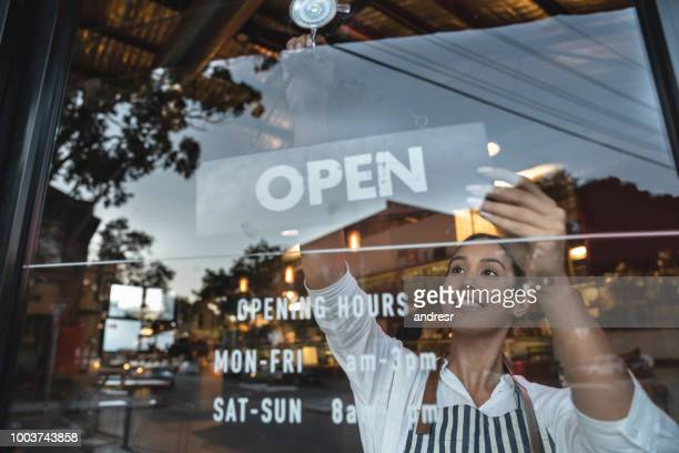 happy business owner hanging an open sign at a restaurant - open sign stock pictures, royalty-free photos & images