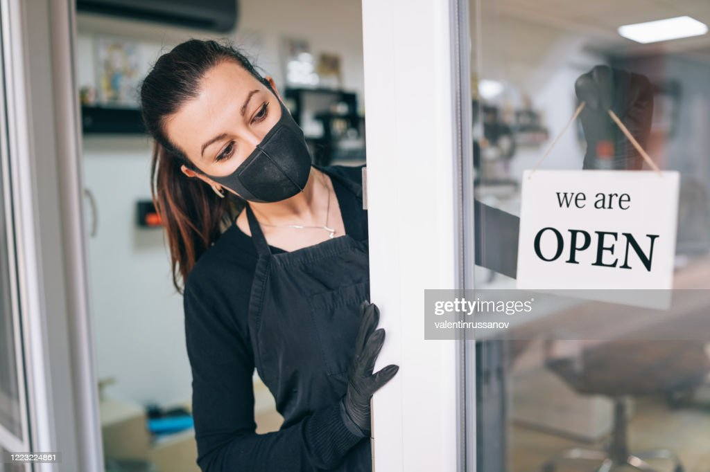 Happy business owner hanging an open sign during COVID-19 : Stock Photo