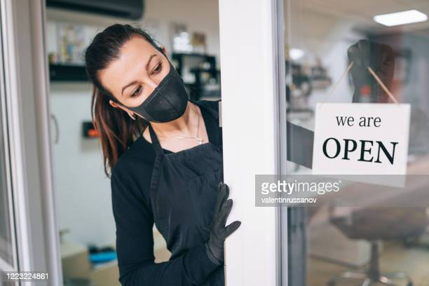 happy business owner hanging an open sign during covid-19 - reopening stock pictures, royalty-free photos & images