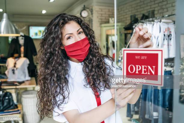 happy business owner hanging an open sign during covid-19 - opening event stock pictures, royalty-free photos & images