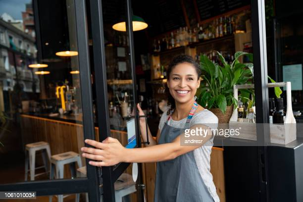 happy business owner opening the door at a cafe - business owner stock pictures, royalty-free photos & images