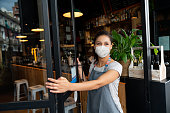 Happy business owner opening the door at a cafe wearing a facemask