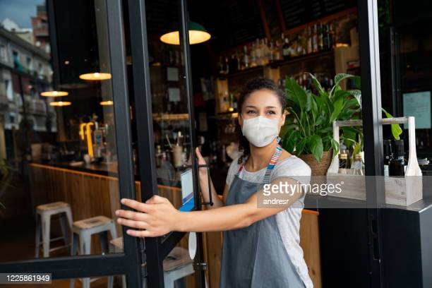 happy business owner opening the door at a cafe wearing a facemask - business owner stock pictures, royalty-free photos & images