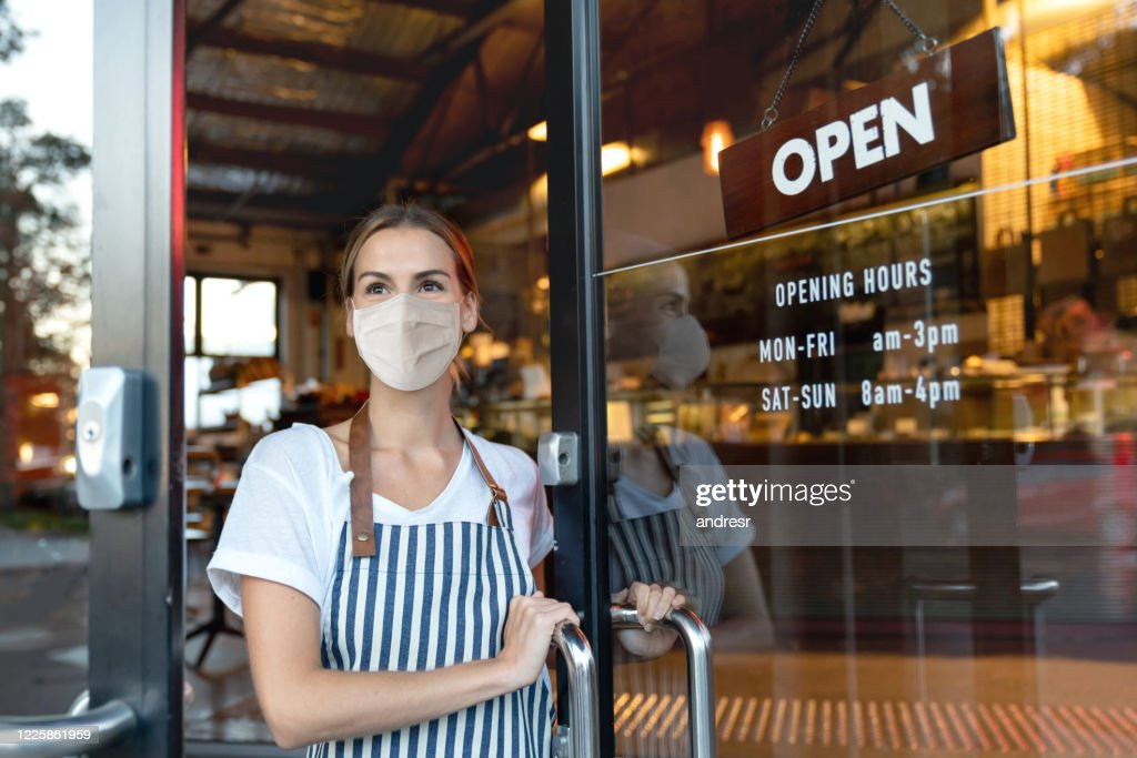 Happy business owner opening the door at a cafe wearing a facemask : Stock Photo