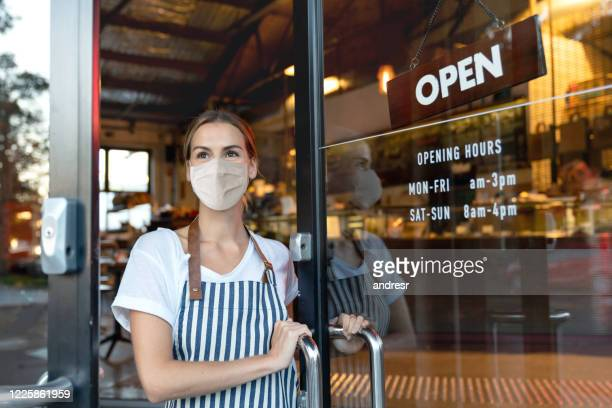 happy business owner opening the door at a cafe wearing a facemask - restaurant stock pictures, royalty-free photos & images