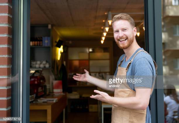 happy business owner welcoming customers at a cafe - bella ciao foto e immagini stock