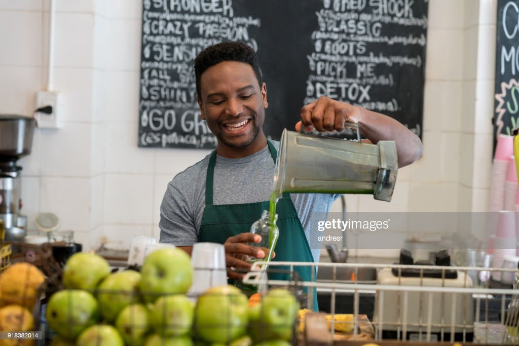 Happy Business Owner Working At His Juice Bar Serving A