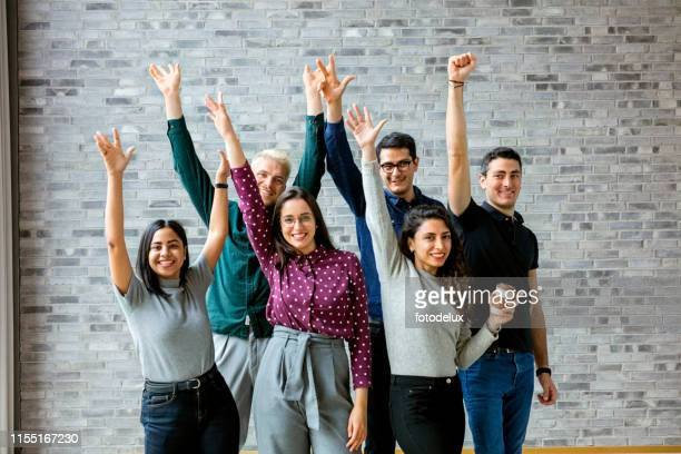 gens heureux d'affaires célébrant le succès au bureau - photo de groupe photos et images de collection