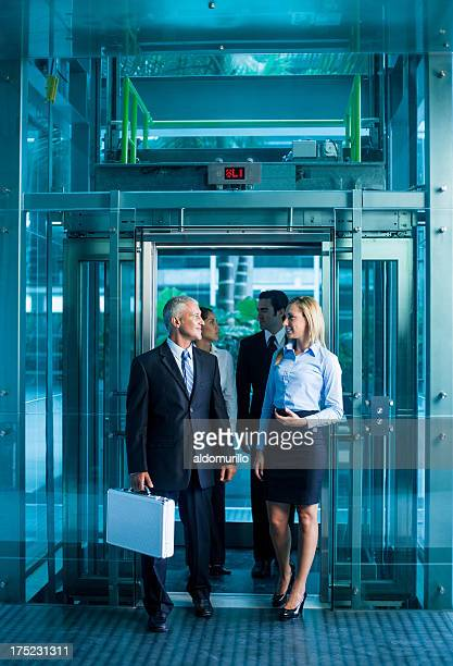 Happy business people coming out of the elevator