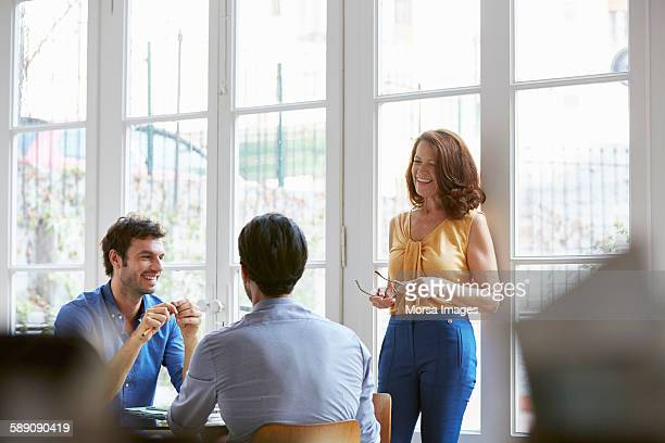 happy business people discussing in office - vanguardians stock pictures, royalty-free photos & images
