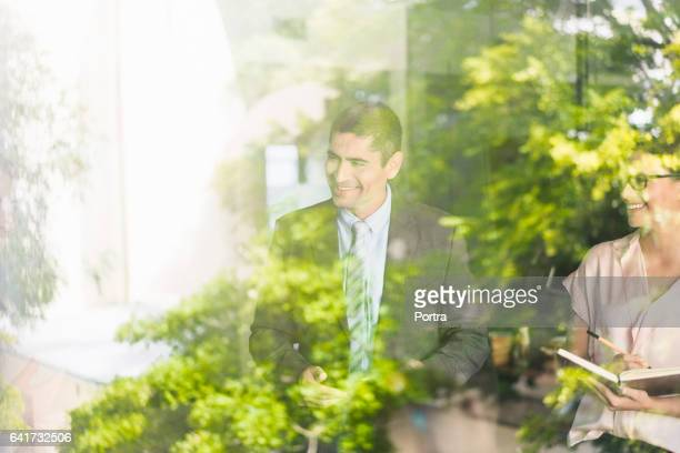 happy business people in office seen through glass - green color stock pictures, royalty-free photos & images