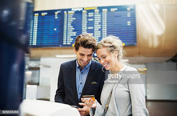 Happy business people looking at credit card in airport