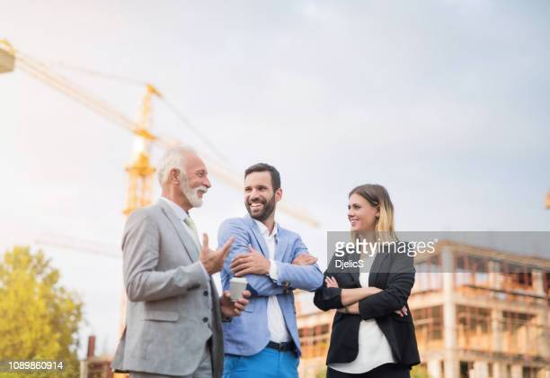 happy business people on a construction site. - real estate stock pictures, royalty-free photos & images