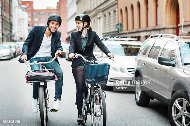 Happy business people riding bicycles on city street