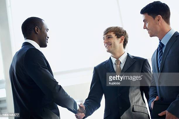Happy business people shaking hands on a deal and smiling