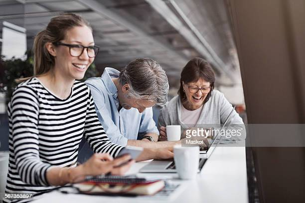 Happy business people sitting at counter in office