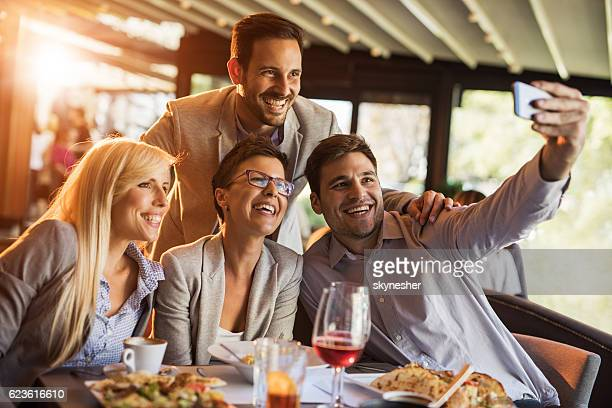 happy business people taking selfie during lunch break in restaurant. - businesswear stock pictures, royalty-free photos & images