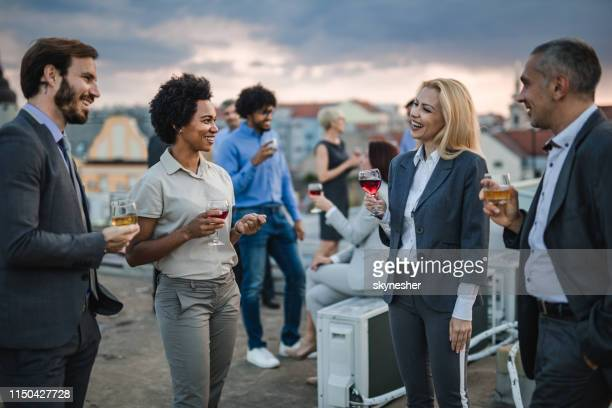 happy business people talking while drinking alcohol on a rooftop party. - businesswear stock pictures, royalty-free photos & images