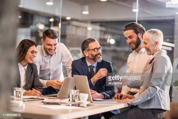 equipe feliz do negócio que comunica-se ao trabalhar em computadores no escritório. - reunião de equipe - fotografias e filmes do acervo