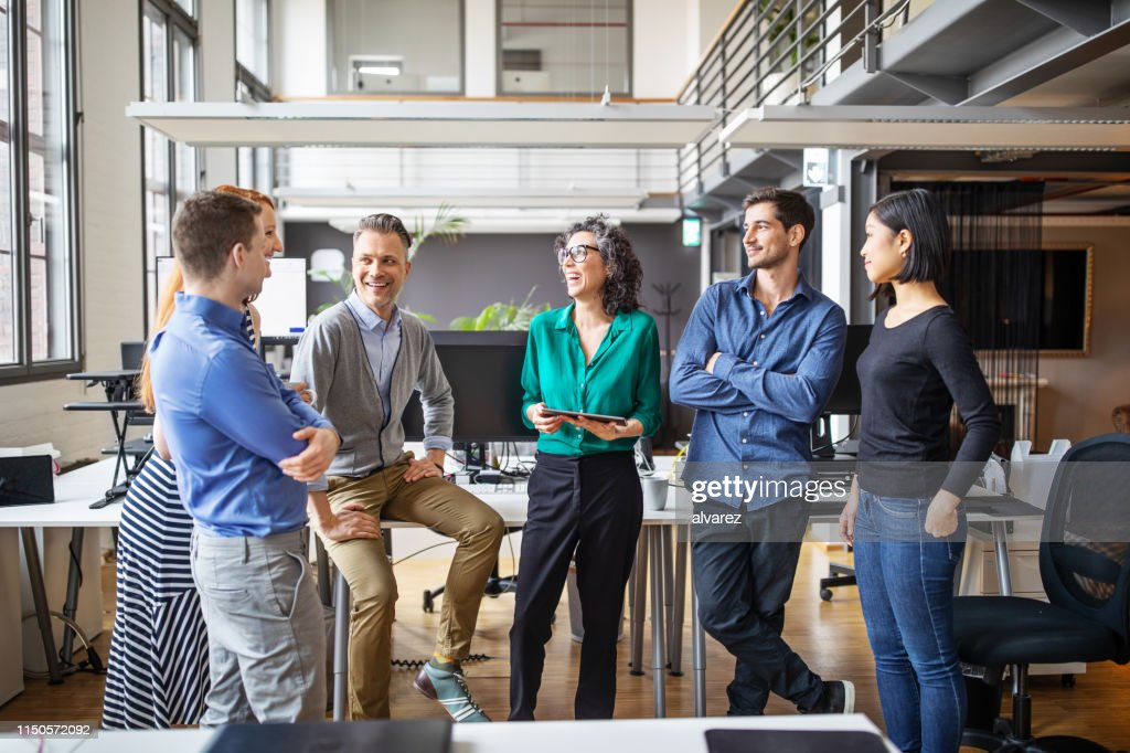 Happy business team having a standing meeting in office : Stock Photo