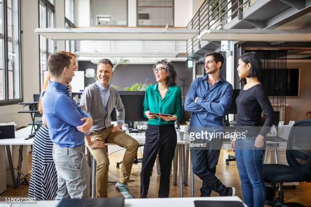 happy business team met een permanente meeting in office - teamwerk stockfoto's en -beelden