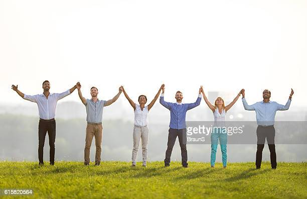 Happy business team holding hands on a meadow.