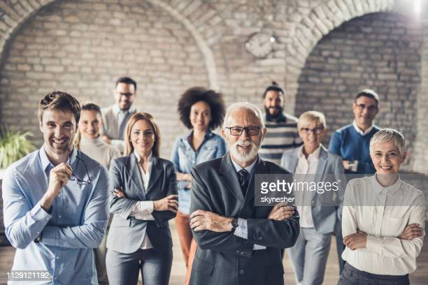 happy business team standing in the office and looking at camera. - organized group photo stock pictures, royalty-free photos & images
