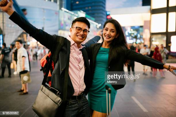 happy business traveller having fun together arriving in kuala lumpur - downtown comedy duo stock pictures, royalty-free photos & images