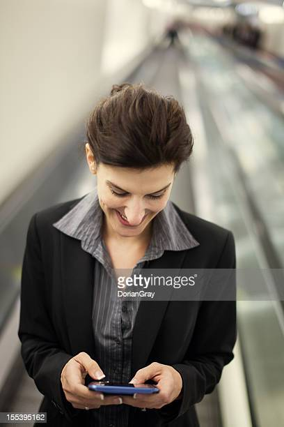 Happy business woman texting