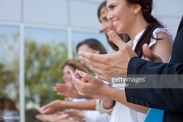 Happy business woman with colleagues applauding