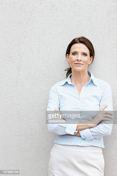 happy business woman with hands folded leaning on a wall - open collar stock photos and pictures