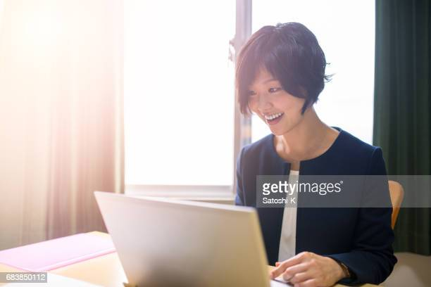 Happy business woman working in meeting room, using laptop
