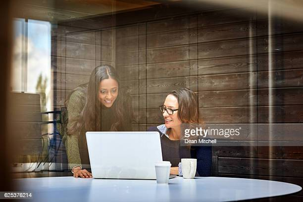 Happy business women working together on laptop