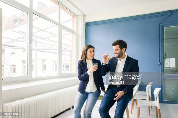 happy businessman and businesswoman with drinks in office - ジャケット ストックフォトと画像