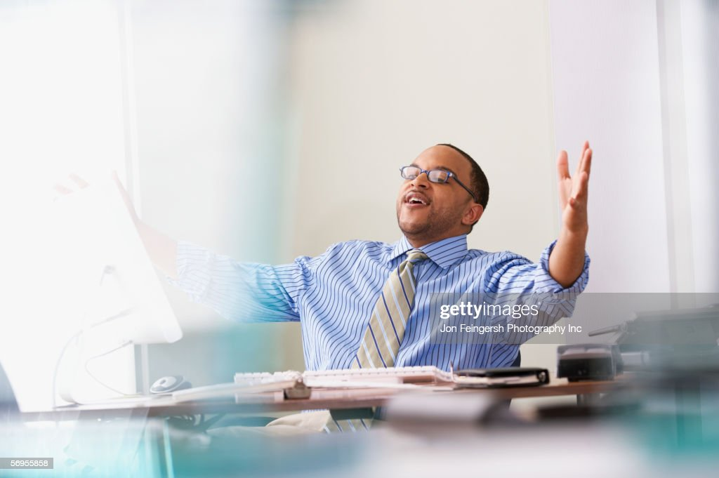 Happy businessman at desk : Stock Photo