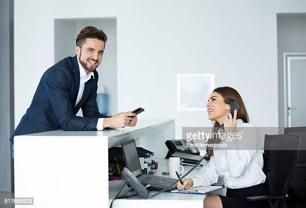 Happy businessman at receptionist desk looking at camera.