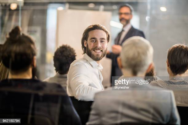 Happy businessman attending a training class in a board room.