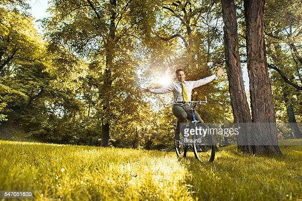 Happy businessman balancing while cycling in the park.