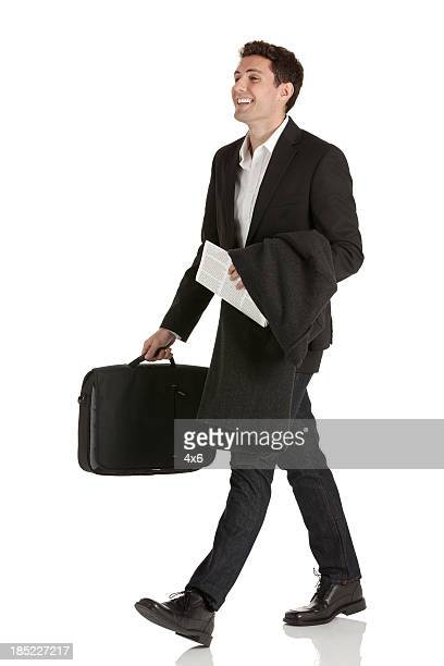 Happy businessman carrying a suitcase