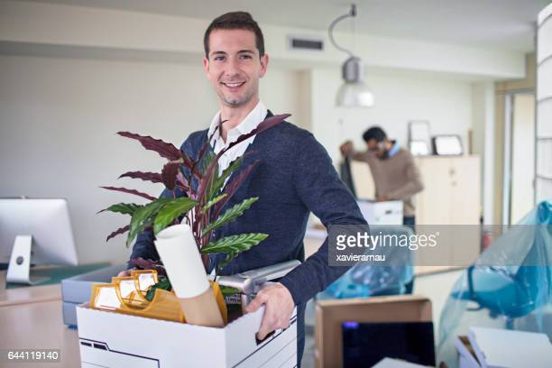 Happy businessman carrying crate in new office