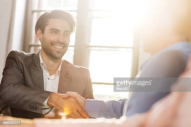 Happy businessman come to an agreement with his colleague.