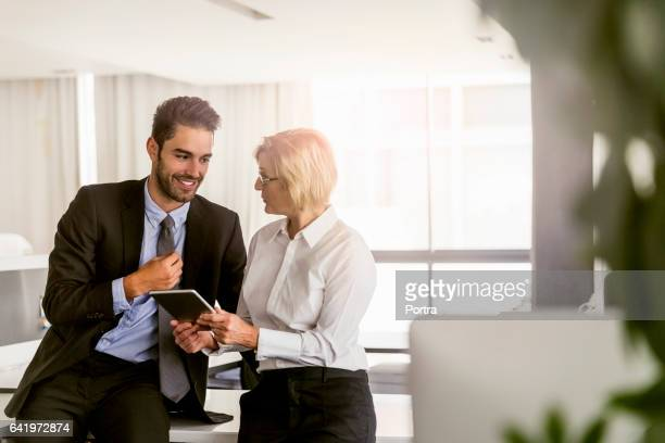 happy businessman discussing with colleague - older woman younger man stock photos and pictures
